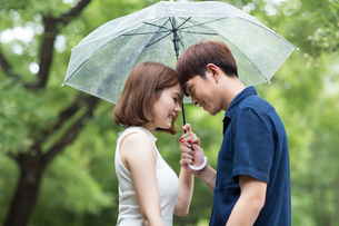 Young couple holding umbrellaの写真素材 [FYI02229005]