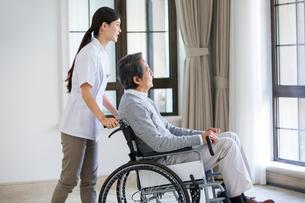 Nursing assistant taking care of senior man in wheel chairの写真素材 [FYI02229009]