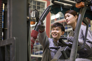 Confident workers driving forklift in the factoryの写真素材 [FYI02229043]