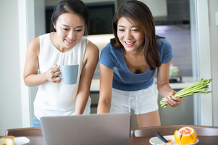 Best female friends using laptop for online recipeの写真素材 [FYI02229110]