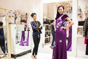 Chinese fashion designer examining dress on customerの写真素材 [FYI02229112]