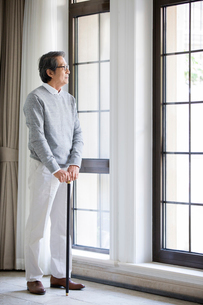 Senior man looking out windowの写真素材 [FYI02229116]