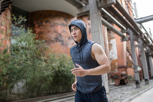Young Chinese man jogging outdoorsの写真素材 [FYI02229130]