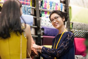 Chinese fashion designer helping customer choosing fabric swatchの写真素材 [FYI02229169]