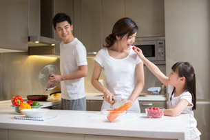 Happy young family cooking in kitchenの写真素材 [FYI02229225]