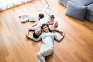 Happy young family resting on wooden floorの写真素材 [FYI02229267]