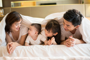 Happy young family lying on bedの写真素材 [FYI02229289]