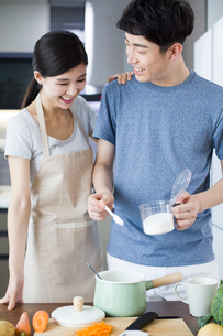 Happy young couple cooking in kitchenの写真素材 [FYI02229300]