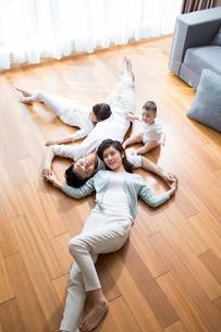 Happy young family resting on wooden floorの写真素材 [FYI02229302]