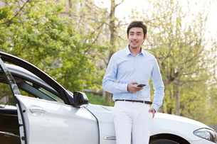 Young man leaning on car with smart phoneの写真素材 [FYI02229314]