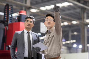 Businessman and engineer talking in the factoryの写真素材 [FYI02229337]