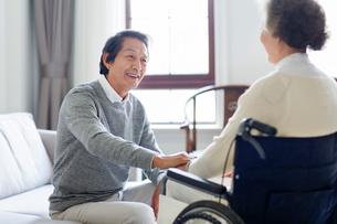 Senior man taking care of wife in wheel chairの写真素材 [FYI02229343]