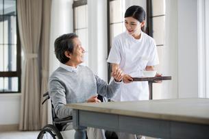 Nursing assistant taking care of senior man in wheel chairの写真素材 [FYI02229345]