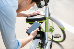 Young man scanning a QR code to unlock a share bikeの写真素材 [FYI02229378]