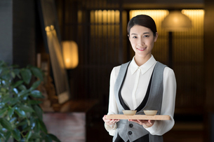 Elegance Chinese waitress holding two cups of teaの写真素材 [FYI02229403]