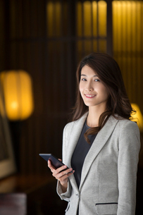 Cheerful young Chinese businesswoman holding a smart phoneの写真素材 [FYI02229424]