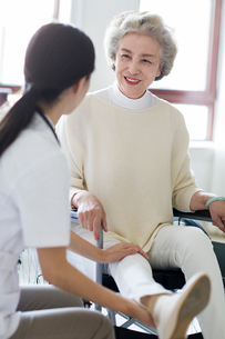 Nursing assistant taking care of senior woman in wheel chairの写真素材 [FYI02229451]