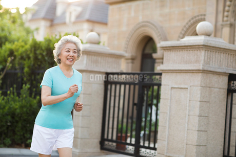 Cheerful senior Chinese woman jogging outsideの写真素材 [FYI02229494]