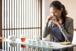 Mature Chinese woman drinking teaの写真素材 [FYI02229506]