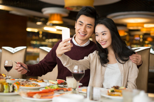 Cheerful young Chinese couple having buffet dinnerの写真素材 [FYI02229510]