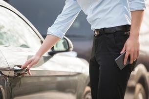 Young businessman opening car doorの写真素材 [FYI02229520]