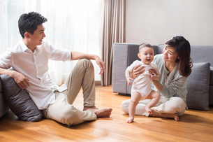 Happy young family sitting on wooden floorの写真素材 [FYI02229521]