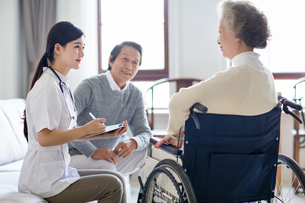 Nursing assistant taking care of senior woman in wheel chairの写真素材 [FYI02229582]