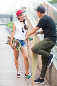 Cheerful young Chinese couple with skateboard talkingの写真素材 [FYI02229595]
