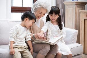 Cheerful Chinese grandmother and grandchildren looking at photo albumの写真素材 [FYI02229611]
