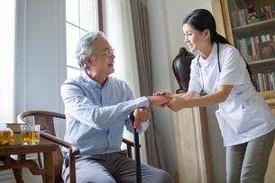 Nursing assistant taking care of senior manの写真素材 [FYI02229618]