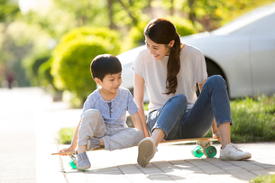 Chinese mother and son sitting on a skateboardの写真素材 [FYI02229622]