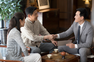 Confident Chinese financial consultant shaking hands with mature coupleの写真素材 [FYI02229626]