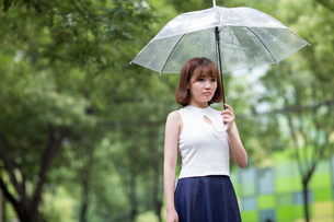 Sullen young woman holding umbrellaの写真素材 [FYI02229694]