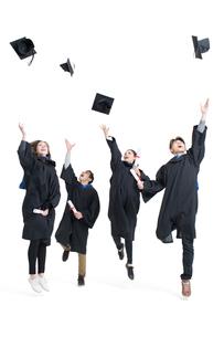 Happy college graduates throwing mortar boardsの写真素材 [FYI02229721]