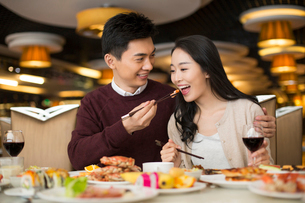 Cheerful young Chinese couple having buffet dinnerの写真素材 [FYI02229742]