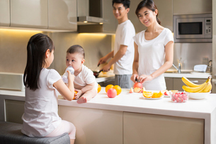 Happy young family cooking in kitchenの写真素材 [FYI02229749]