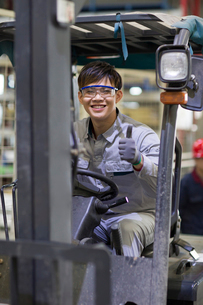 Young workman driving forklift in the factoryの写真素材 [FYI02229754]