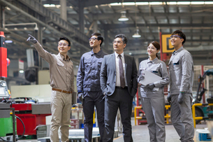 Confident businessman and engineering team in the factoryの写真素材 [FYI02229761]