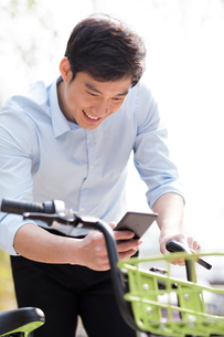 Young man scanning a QR code to unlock a share bikeの写真素材 [FYI02229766]