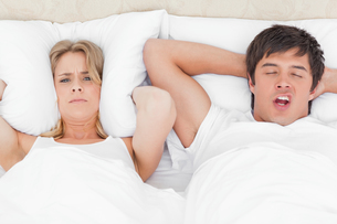 Woman is very angry with the mans snoring and has a pillow over her earsの写真素材 [FYI02229779]
