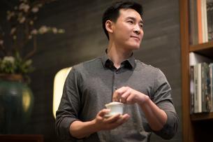 Mid adult Chinese man drinking teaの写真素材 [FYI02229826]