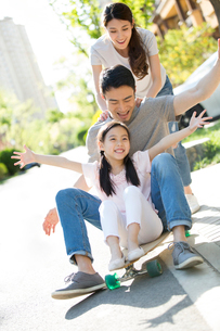 Happy young Chinese family playing with skateboardの写真素材 [FYI02229849]