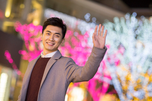 Cheerful young Chinese man wavingの写真素材 [FYI02229867]