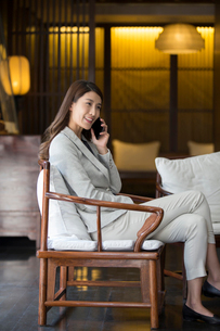 Cheerful young Chinese businesswoman talking on cell phoneの写真素材 [FYI02229898]