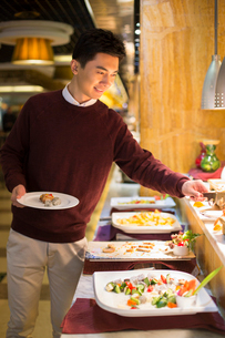 Cheerful young Chinese man taking food from buffet tableの写真素材 [FYI02229970]
