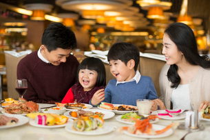 Cheerful young Chinese family having buffet dinnerの写真素材 [FYI02230023]