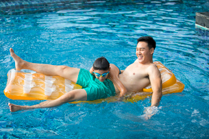 Happy Chinese father and son having fun in swimming poolの写真素材 [FYI02230045]