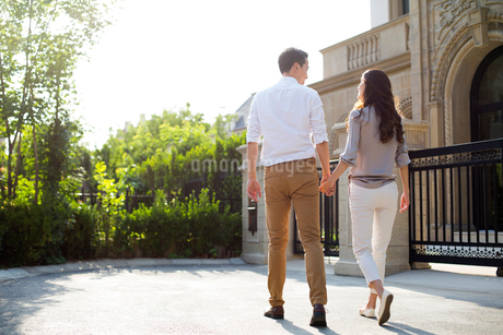 Cheerful young Chinese couple holding hands walkingの写真素材 [FYI02230050]