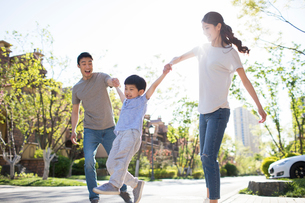 Happy young Chinese family playing outdoorsの写真素材 [FYI02230064]