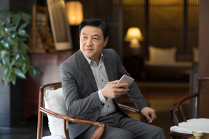 Cheerful Chinese businessman holding a smart phoneの写真素材 [FYI02230067]